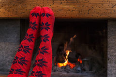 Feet in wool socks warming by cozy fire Stock Images