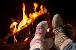 Feet in wool socks warming at the fireplace Stock Images