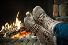 Feet in wool socks warming at the fireplace royalty free stock photography