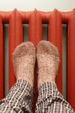 Feet with wool socks warming on the radiator. Feet with wool socks warming on the red cast iron radiator Royalty Free Stock Images