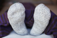 Feet in woolen socks. Covered with blanket Royalty Free Stock Photography