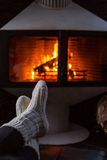 Feet in woolen socks by fireplace. Woman sitting at a cosy fire warming her cold feet. Christmas and winter mood. Woman sitting at a cosy fire warming her cold Stock Photo