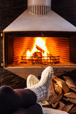 Feet in woolen socks by fireplace. Woman sitting at a cosy fire warming her cold feet. Christmas and winter mood. Woman sitting at a cosy fire warming her cold Royalty Free Stock Image