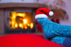 Feet in woollen blue socks and Santa hat . Royalty Free Stock Images