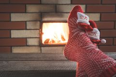Feet in woollen red socks by the fireplace. Close up on feet. Tabletop for display your christmas product. Feet in woollen red socks by the fireplace. Female Royalty Free Stock Photos