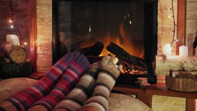 Feet in woollen socks by the burning Christmas cozy fireplace. 4K. Couple relaxes by warm fire and warming up their feet. Winter and Christmas holidays concept stock video footage