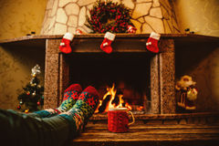 Feet in woollen socks by the Christmas fireplace. Woman relaxes. By warm fire with a cup of hot drink and warming up her feet in woollen socks. Close up on feet Stock Photography
