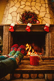 Feet in woollen socks by the Christmas fireplace. Woman relaxes. By warm fire with a cup of hot drink and warming up her feet in woollen socks. Close up on feet Royalty Free Stock Photography
