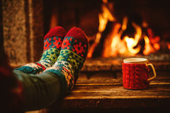 Feet in woollen socks by the Christmas fireplace. Woman relaxes. By warm fire with a cup of hot drink and warming up her feet in woollen socks. Close up on feet Royalty Free Stock Photo