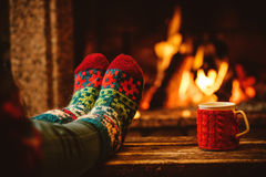 Feet in woollen socks by the Christmas fireplace. Woman relaxes. By warm fire with a cup of hot drink and warming up her feet in woollen socks. Close up on feet Stock Images