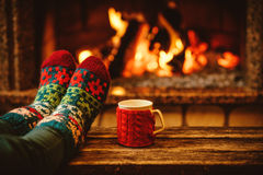 Feet in woollen socks by the Christmas fireplace. Woman relaxes. By warm fire with a cup of hot drink and warming up her feet in woollen socks. Close up on feet Stock Photos