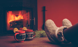 Feet in woollen socks by the Christmas fireplace. Woman relaxes. By warm fire with a cup of hot drink and warming up her feet in woollen socks. Close up on feet Royalty Free Stock Image