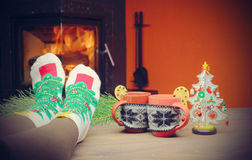Feet in woollen socks by the Christmas fireplace. Woman relaxes. By warm fire with a cup of hot drink and warming up her feet in woollen socks. Close up on feet Royalty Free Stock Photos