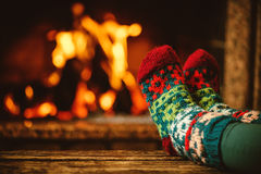 Feet in woollen socks by the fireplace. Woman relaxes by warm. Fire and warming up her feet in woollen socks. Close up on feet. Winter and Christmas holidays Royalty Free Stock Image