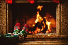 Feet in woollen socks by the fireplace. Woman relaxes by warm. Fire and warming up her feet in woollen socks. Close up on feet. Winter and Christmas holidays Royalty Free Stock Photos