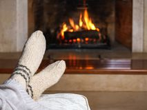 Feet in woollen socks and knitted plaid in front of the fireplace. Close up on feet. Cozy relaxed magical atmosphere home interior. Christmas New Year holidays stock photo