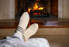 Feet in woollen socks and knitted plaid in front of the fireplace. Close up on feet. Cozy relaxed magical atmosphere home interior royalty free stock images