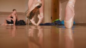 Feet of young ballerinas in pointe shoes close-up. Against the backdrop of a ballet class stock video