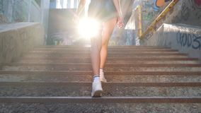 Feet of a young beautiful girl. She goes up the stairs 4k. stock footage