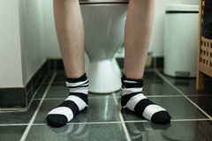 Feet of young boy sat on toilet Royalty Free Stock Photo