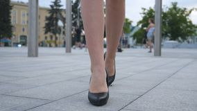 Feet of young business woman in high-heeled footwear going in the city. Female legs in high heels shoes walking in the Stock Images