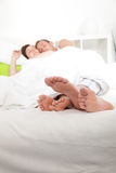 Feet of a young couple sleeping in bed. View from the bottom of the bed of the bare feet of a young couple sleeping in bed sticking out from under the bedclothes Royalty Free Stock Photos