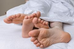 Feet of young couple is sleeping together in bed.  Royalty Free Stock Photos