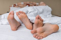 Feet of young couple is sleeping together in bed.  Royalty Free Stock Images
