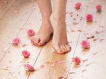 Feet of a young female on a wooden floor stock images