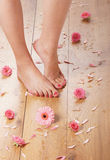 Feet of a young female on a wooden floor Stock Photos