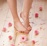 Feet of a young female on a wooden floor Royalty Free Stock Photos