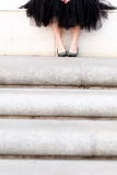 Feet of young lady in a tutu sitting above stairs. Focus on young lady's feet in sparkly flats and tutu as she waits on a concrete bench above a flight of stairs Royalty Free Stock Photography