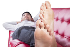 Feet of young man lying on couch Stock Photography