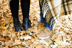 Feet of a young pair. Stand on autumn foliage Royalty Free Stock Photos
