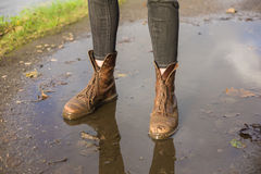 Feet of young person standing in puddle Stock Photo