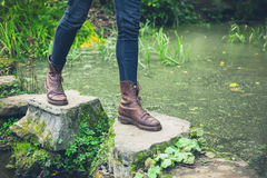 Feet of young person on stepping stones in a pond. Royalty Free Stock Image