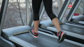 Feet of young sportive woman running fast on treadmill, training for wellness. Stock footage stock footage