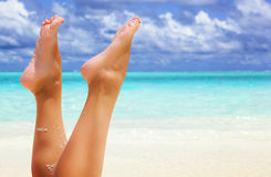 Feet of a young woman on background of ocean Royalty Free Stock Image