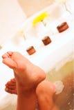 Feet of a young woman in a bath. White bath tab with tanned feet of a young woman Royalty Free Stock Image