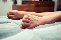 Feet of young woman on bed at home Stock Photo