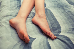 Feet of young woman on bed at home Royalty Free Stock Image
