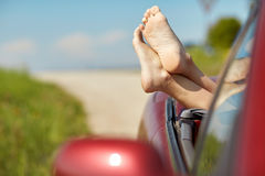 Feet of young woman in convertible car at summer Stock Photography