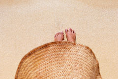 A feet of a young woman in a hat seating down on a sandy beach. And sun bathing on a sunny summer day Stock Images