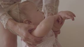 Feet of a young woman and her baby standing on the floor at home close-up. The child trying to walk, mom holding her stock footage