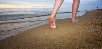 Feet of young woman jogging. On the beach at sunrise Stock Photos