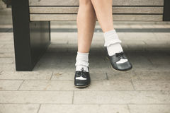 Feet of young woman relaxing on bench in city Royalty Free Stock Photography