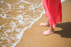 Feet of a young woman on a sandy beach Stock Photography
