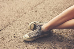 The feet of a young woman sitting in the street Royalty Free Stock Photos