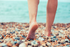 The feet of a young woman standing on the beach Royalty Free Stock Photography