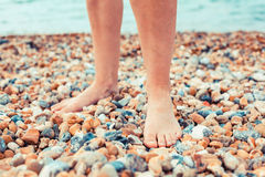 The feet of a young woman standing on the beach Royalty Free Stock Photo